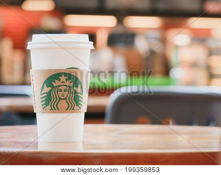 BANGKOK , THAILAND, 1 JULY 2017 : A Cup of Starbucks hot beverage coffee on the table in the Starbucks drive thru shop. Starbucks is the world's largest coffeehouse company.