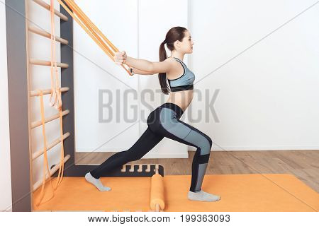 Female training in gym body workout pull ropes