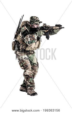 Special forces United States in Camouflage Uniforms studio shot. Holding weapons, wearing jungle hat, shooting on the move, attacking enemy. Studio shot isolated