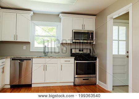 Gourmet Kitchen Features White Shaker Cabinets With Marble Countertops,