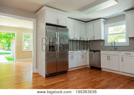 White Kitchen Interior With Sink, Cabinets, And Hardwood Floors