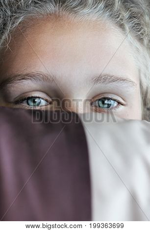 Beautiful girl with blue eyes is hiding her face by striped pillow.