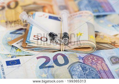 Syringes and wad of euros banknotes bills cash. Cost of health medicine drug. Close-up.