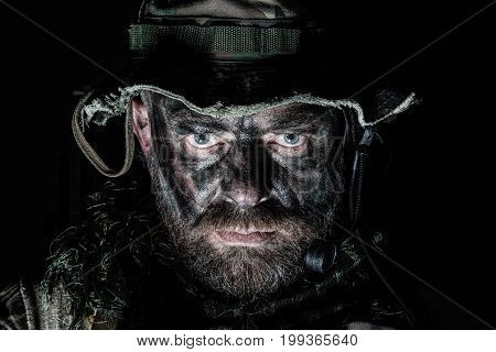 Special forces United States in Camouflage Uniforms studio shot. Wearing jungle hat, Shemagh scarf, painted face. Black background, bottom light