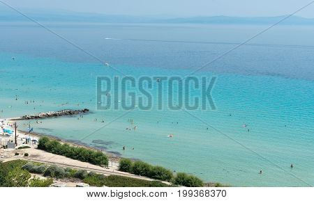 Chalkidiki Greece- July 26 2017: Panoramic view of famous and idyllic beach of Kalithea with people swimming resting and enjoying their summer vacations Kassandra Peninsula in Chalkidiki Greece