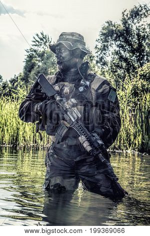 Bearded soldier of special forces in action during river raid in the jungle terrain. He is waist deep in the water and mud and ready to meet enemy, survive and fight in agressive hostile environment