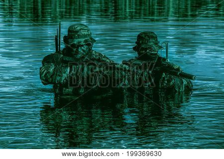 Pair of soldiers in action during river raid in the jungle in the night waist deep in the water and mud and covering each other