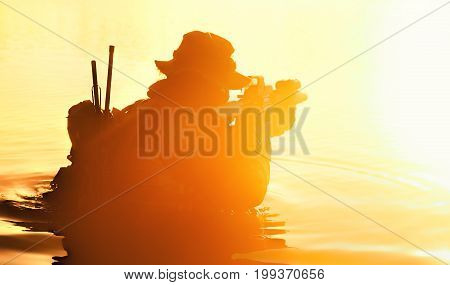 Silhouette of special forces with rifle in action during river raid in the jungle waist deep in the water