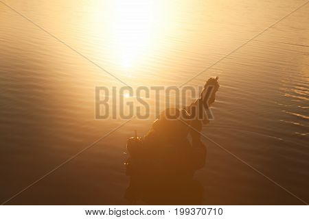 Silhouette of special forces with rifle in action during river raid in the jungle waist deep in the water. View from above