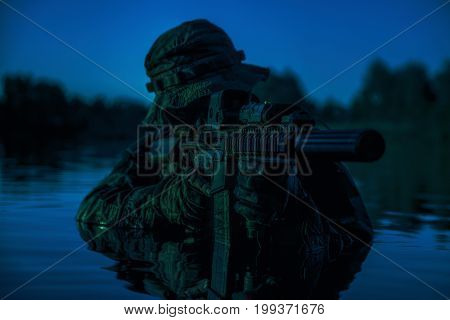 Silhouette of special forces with rifle in action during river raid in the jungle waist deep in the water. Under cover of darkness