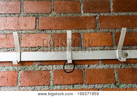 metal clothes hanger on brick wall with hairband