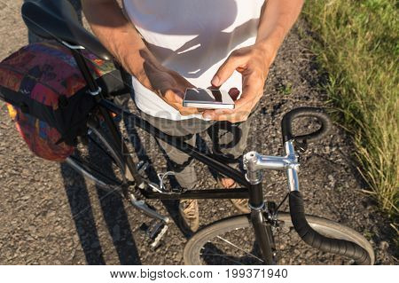 Cycling tourist looking map in smartphone for direction. Bicycle rider on the road uses smartphone to find the way to go