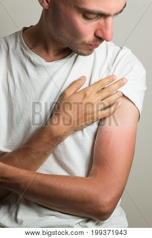 Unhappy male person looking at bad sun-tan. Discontent man examines farmer's tan on his hands