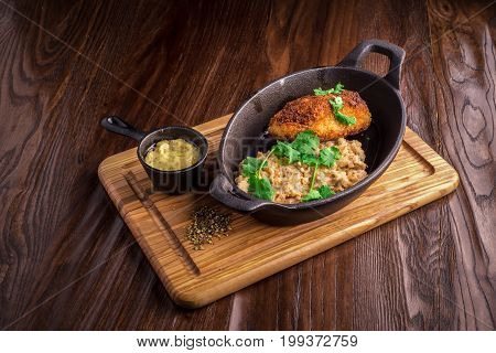 Buckwheat with patties in the frying pan on a wood
