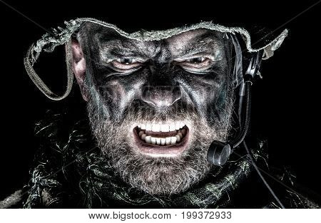 United States Commando face studio shot. Mouth opened, soldier yelling, emitting intimidate formidable frightening scream. Closeup portrait, cropped, isolated, bottom light