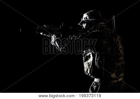 Bearded Special forces United States in Camouflage Uniforms studio shot half length black background, backlit. He is shooting killing enemy, pointing the rifle