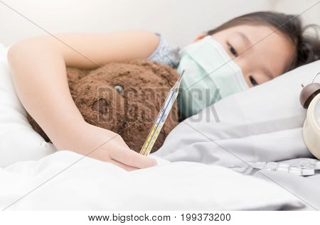 Sick Girl Laying On Bed And Holding Thermometer In Hand