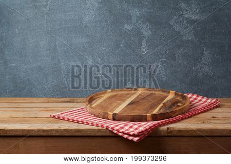 Wooden tray with checked tablecloth on table over blackboard background