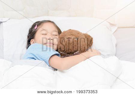 Cute Little Asian Girl Sleep And Hug Teddy Bear On Bed