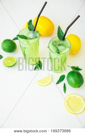 Transparent refreshing cucumber drink with limes and lemons