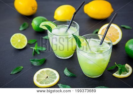 Citrus refreshing lemonade with limes, ice and lemons in glasses
