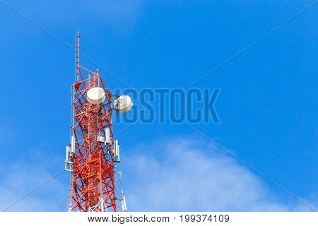 Telecommunication tower in cellular network. Blue sky with clouds background.