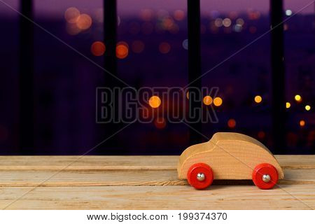 Car insurance concept. Wooden toy car over night bokeh background