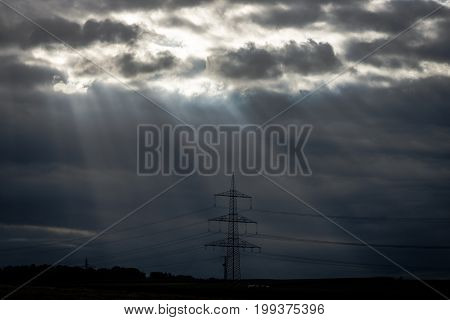 Rays of light making their way through dense clouds. Evening landscape. Agricultural land and power transmission lines.