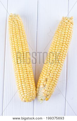 Two raw maize cobs at white wooden table background
