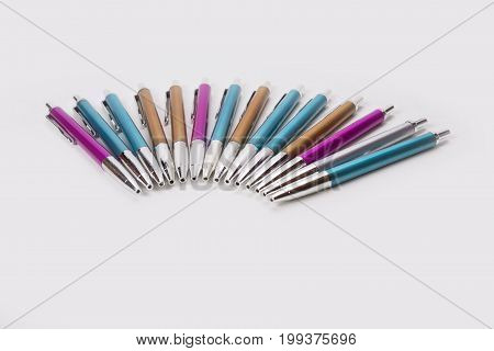 Blue pink and brown ballpoint pens on white background