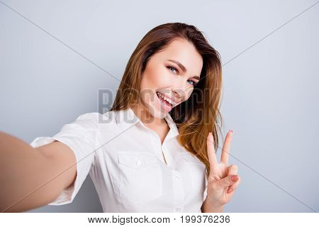 Selfie time! Funky mood. Attractive young lady is making a selfie on the camera flirty and playful. Gesturing v sign standing on pure light grey background