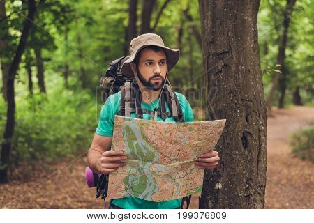 Male brunet bearded confused tourist got lost in the forest holding map looking far trying to find the way. He has a backpack all needed for overnight stay. Search the trail way