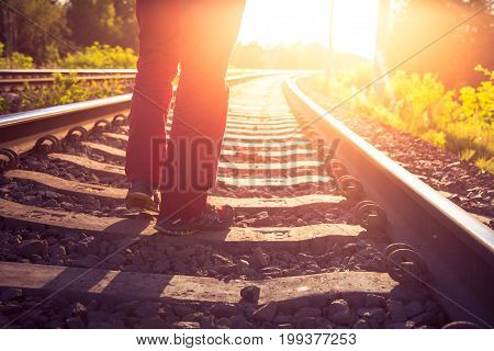 A man going away on the rails against the sunset.