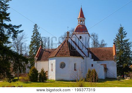 Traditional local Estonian Lutheran church. White stone and red tile roof. poster