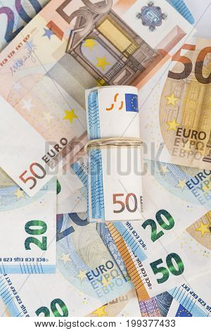 Rolled up wrapped euro banknotes bills cash. Close-up
