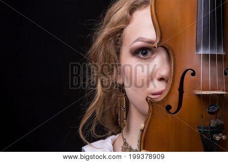 Blond woman hiding behind violin on black background