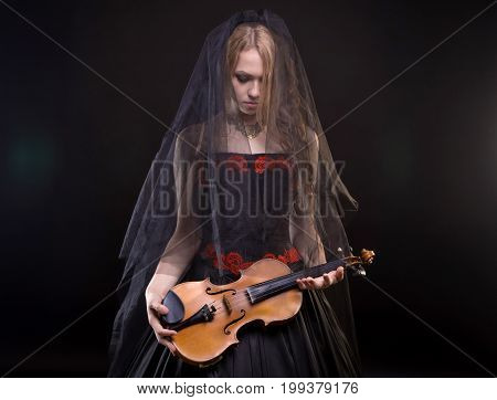 Blond girl with black veil holding fiddle on black background