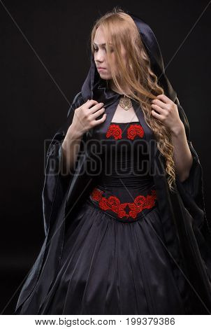 Blond young woman in black cloak on black background