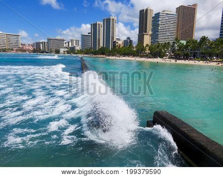 Wave crashing on breakwater wall at Kuhio Beach Lagoon - View of lagoon, beach and hotel skyline - Waikiki Beach, Honolulu, Oahu, Hawaii.