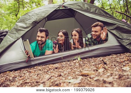 Hello From The Camp Vacation! Four Joyful Friends Are Waving To The Camera In A Tablet, Lying In The