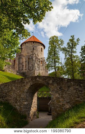 Stoned bridge and beautiful ruins of ancient Livonian castle in old town of Cesis, Latvia. Greenery and summer daytime.