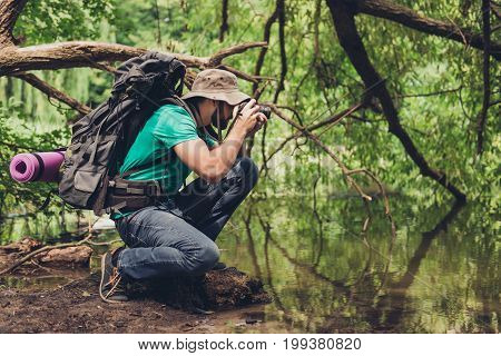 Male photographer is near the lake outdoors in the spring wood taking shot of beautiful nature! He is a tourist hiking in jungle
