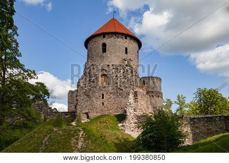Big tower and beautiful ruins of ancient Livonian castle in old town of Cesis, Latvia. Greenery and summer daytime.