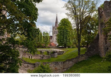 Wooden bridge, cathedral and green park around beautiful ruins of ancient Livonian castle in old town of Cesis, Latvia. Greenery and summer daytime.