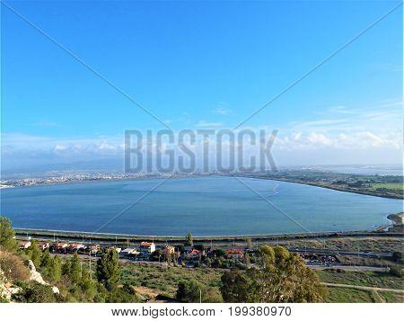 Paesaggio rurale con citta, mare, cielo e nuvole