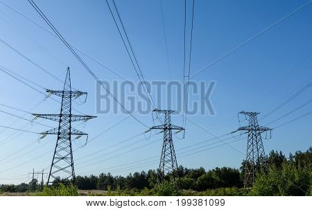 Electricity pylons going into the distance over summertime countryside.