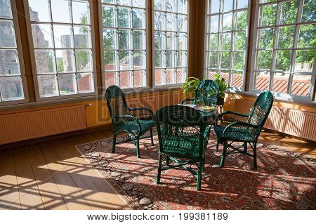 Bright room in cottage with wicker rattan chairs and table. Big windows and sunlight.