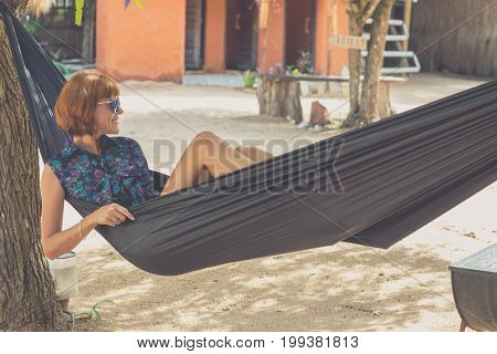 Beautiful Sexy Woman With Sunglasses Relaxing In Hammock In Nature. Person Relaxation Concept. Bali