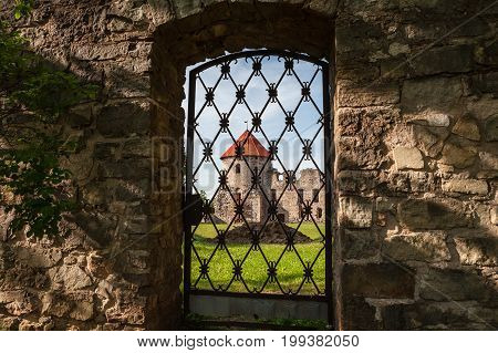 Old wall and tower through iron grid. Ruins of the ancient castle in old town of Cesis, LAtvia