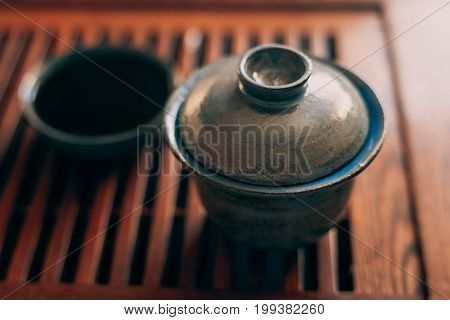 Chinese tea cup or Gaiwan on wooden tea table, selective focus, toned